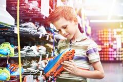 Αγόρι με τις μπότες ποδοσφαίρου στο αθλητικό κατάστημα στοκ εικόνες