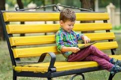 Αγόρι με τον υπολογιστή ταμπλετών στο πάρκο Στοκ Φωτογραφία