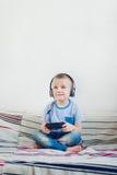 Αγόρι με το ακουστικό που παίζει τα τηλεοπτικά παιχνίδια Στοκ εικόνα με δικαίωμα ελεύθερης χρήσης