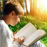 Αγόρι με το βιβλίο υπαίθριο Στοκ Φωτογραφίες