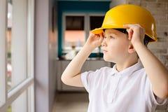 Αγόρι με το κίτρινο κράνος στο σπίτι Στοκ φωτογραφία με δικαίωμα ελεύθερης χρήσης