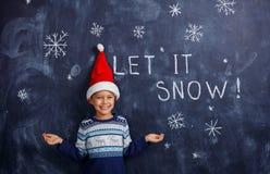 Αγόρι με το καπέλο Santa με το χιόνι Στοκ φωτογραφία με δικαίωμα ελεύθερης χρήσης