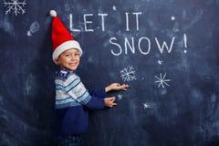 Αγόρι με το καπέλο Santa με το χιόνι Στοκ Εικόνες
