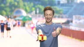 Αγόρι με το κιβώτιο δώρων που παρουσιάζει αντίχειρα απόθεμα βίντεο