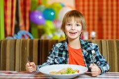 Αγόρι με το μαχαίρι και δίκρανο μπροστά από τη σαλάτα Στοκ Εικόνες