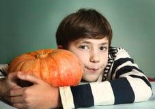 Αγόρι με το μεγάλο πορτοκαλί στενό επάνω πορτρέτο κολοκύθας Στοκ Εικόνες