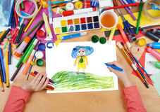 Αγόρι με το μπλε καπέλο στο τοπ σχέδιο παιδιών λόφων λιβαδιών, τοπ χέρια άποψης με την εικόνα ζωγραφικής μολυβιών σε χαρτί, εργασ Στοκ εικόνα με δικαίωμα ελεύθερης χρήσης
