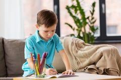 Αγόρι με το σημειωματάριο και μολύβια που σύρουν στο σπίτι Στοκ φωτογραφία με δικαίωμα ελεύθερης χρήσης
