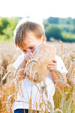 Αγόρι με το ψωμί πέρα από το κεφάλι σας στο ώριμο σιτάρι με το s Στοκ Εικόνα