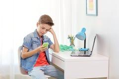 Αγόρι με το smartphone που φοβερίζεται από το μήνυμα κειμένου Στοκ εικόνες με δικαίωμα ελεύθερης χρήσης