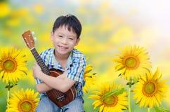 Αγόρι με το ukulele στον κήπο Στοκ φωτογραφίες με δικαίωμα ελεύθερης χρήσης