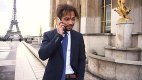 Αγόρι μιγάδων που μιλά με τη φίλη τηλεφωνικώς κοντά στον πύργο του Άιφελ σε σε αργή κίνηση απόθεμα βίντεο