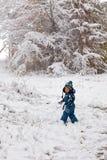 Αγόρι μικρών παιδιών που έχει τη διασκέδαση με το χιόνι τη χειμερινή ημέρα Στοκ Εικόνα