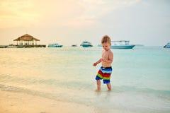 Αγόρι μικρών παιδιών τριάχρονων παιδιών στην παραλία στο ηλιοβασίλεμα στοκ εικόνες με δικαίωμα ελεύθερης χρήσης