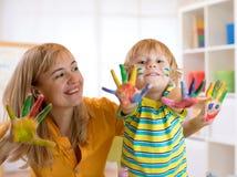 Αγόρι παιδιών και το mom του με τα χρωματισμένα χέρια Παιδί που σύρει και που χρωματίζει με το δάσκαλο στο κέντρο ή το playschool Στοκ Εικόνες