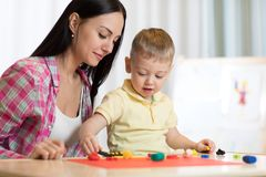 Αγόρι παιδιών παιδιών και το mom του που παίζουν το ζωηρόχρωμο παιχνίδι αργίλου στο βρεφικό σταθμό ή τον παιδικό σταθμό Στοκ φωτογραφία με δικαίωμα ελεύθερης χρήσης