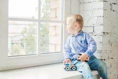 αγόρι παιδιών που φαίνεται έξω παράθυρο στο σπίτι Στοκ εικόνα με δικαίωμα ελεύθερης χρήσης