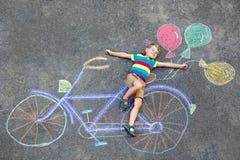 Αγόρι παιδάκι που έχει τη διασκέδαση με την εικόνα κιμωλιών ποδηλάτων Στοκ Φωτογραφία