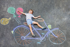 Αγόρι παιδάκι που έχει τη διασκέδαση με την εικόνα κιμωλιών ποδηλάτων Στοκ φωτογραφία με δικαίωμα ελεύθερης χρήσης