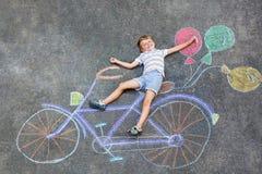 Αγόρι παιδάκι που έχει τη διασκέδαση με την εικόνα κιμωλιών ποδηλάτων στο έδαφος Στοκ Φωτογραφίες
