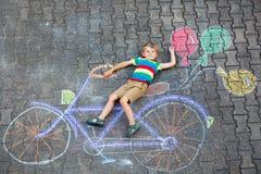 Αγόρι παιδάκι που έχει τη διασκέδαση με την εικόνα κιμωλιών ποδηλάτων στο έδαφος Στοκ εικόνες με δικαίωμα ελεύθερης χρήσης