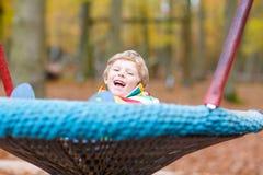 Αγόρι παιδάκι που έχει τη διασκέδαση στην παιδική χαρά φθινοπώρου Στοκ φωτογραφίες με δικαίωμα ελεύθερης χρήσης