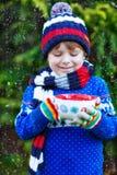 Αγόρι παιδάκι που κρατά το μεγάλο φλυτζάνι με τη σοκολάτα Στοκ Φωτογραφίες