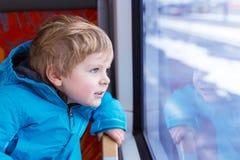 Αγόρι παιδάκι που ταξιδεύει και που φαίνεται έξω παράθυρο τραίνων έξω Στοκ Φωτογραφία