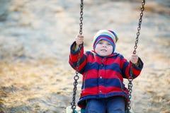 Αγόρι παιδάκι που ταλαντεύεται στην παιδική χαρά υπαίθρια Στοκ Φωτογραφία