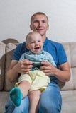 Αγόρι παιδιών και το παιχνίδι πατέρων του με ένα playstation από κοινού Στοκ εικόνα με δικαίωμα ελεύθερης χρήσης