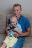 Αγόρι παιδιών και το παιχνίδι πατέρων του με ένα playstation από κοινού Στοκ Εικόνες