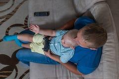 Αγόρι παιδιών και το παιχνίδι πατέρων του με ένα playstation από κοινού Στοκ Φωτογραφία