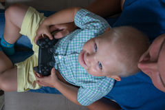 Αγόρι παιδιών και το παιχνίδι πατέρων του με ένα playstation από κοινού Στοκ Φωτογραφίες