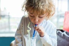 Αγόρι παιδιών με τη σγουρή τρίχα που πίνει milkshake από το γυαλί Στοκ Φωτογραφίες
