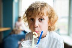 Αγόρι παιδιών με τη σγουρή τρίχα που πίνει milkshake και που εξετάζει τη κάμερα Στοκ Φωτογραφίες