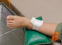 Αγόρι παιδιών με τον επίδεσμο στο πόδι και το νοσοκομειακό κρεβάτι ξαπλώματος Στοκ φωτογραφία με δικαίωμα ελεύθερης χρήσης