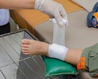 Αγόρι παιδιών με τον επίδεσμο στο πόδι και το νοσοκομειακό κρεβάτι ξαπλώματος Στοκ εικόνες με δικαίωμα ελεύθερης χρήσης