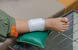 Αγόρι παιδιών με τον επίδεσμο στο πόδι και το νοσοκομειακό κρεβάτι ξαπλώματος Στοκ εικόνα με δικαίωμα ελεύθερης χρήσης
