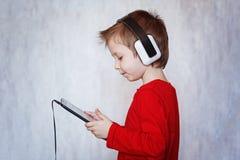 Αγόρι παιδιών που ακούει τον κινηματογράφο μουσικής ή προσοχής με τα ακουστικά α Στοκ εικόνα με δικαίωμα ελεύθερης χρήσης