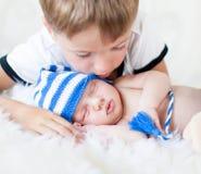 Αγόρι παιδιών που εξετάζει το νεογέννητο αδελφό ύπνου Στοκ φωτογραφία με δικαίωμα ελεύθερης χρήσης
