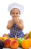 Αγόρι παιδιών που φορά ένα καπέλο αρχιμαγείρων με τα υγιή φρούτα τροφίμων Στοκ Εικόνα