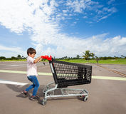 Αγόρι παιδιών που ωθεί το κενό κάρρο αγορών στο χώρο στάθμευσης Στοκ φωτογραφίες με δικαίωμα ελεύθερης χρήσης