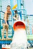 Αγόρι που έχει τη διασκέδαση με τον κάδο νερού Στοκ Εικόνες