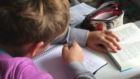 Αγόρι που αγωνίζεται με τη γραπτή εργασία στην κρεβατοκάμαρα απόθεμα βίντεο