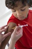Αγόρι που λαμβάνει το εμβόλιο στο βραχίονα στοκ φωτογραφία