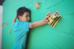 Αγόρι που αναρριχείται στον πράσινο τοίχο Στοκ φωτογραφία με δικαίωμα ελεύθερης χρήσης