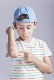 Αγόρι που αντιδρά στον πόνο με τον πληγωμένο βραχίονα Στοκ Φωτογραφία