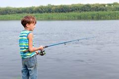 Αγόρι που αλιεύει στον ποταμό, καλοκαίρι στοκ φωτογραφία