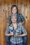 Αγόρι που βοηθά τη μητέρα του που χρωματίζει το υπόστεγο εργαλείων Στοκ φωτογραφία με δικαίωμα ελεύθερης χρήσης