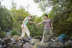 Αγόρι που βοηθά τη φίλη στο πέρασμα του ρεύματος στοκ φωτογραφία